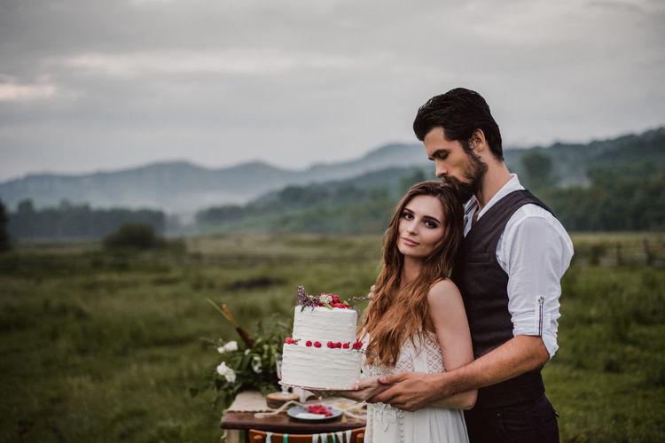 Portrait of bride with bridegroom holding wedding cake on field