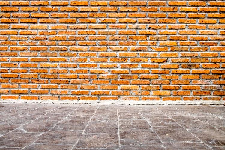 Empty footpath against brick wall