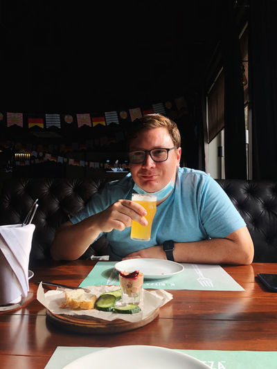 Portrait of man holding drink by food in cafe