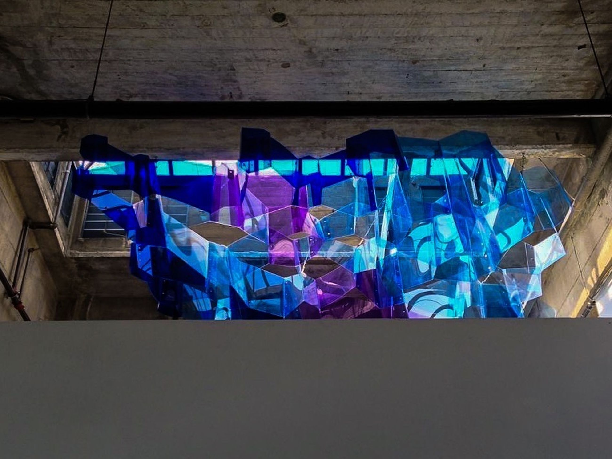 blue, multi colored, art and craft, indoors, art, creativity, wall - building feature, hanging, built structure, wall, architecture, graffiti, no people, variation, colorful, large group of objects, in a row, clothing, wood - material, pattern