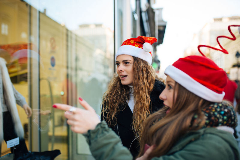 Two attractive young shopaholic with santa claus hats excited looking at shopping window Boutique Business Sale Shopping Standing Window Shopping Buying Communication Consumerism Customer  Gift Hat Lifestyles People Real People Retail  Santas Hat Shopaholic Shopping Bag Shopping Mall Store Store Window Street Window Young Women