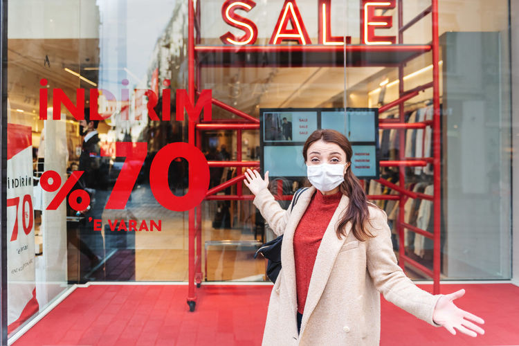 Portrait of happy woman wearing mask standing by shopping mall
