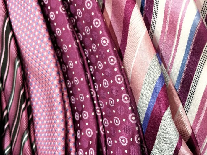 Man's tie colorful pattern background variety many dress clothes formal business attire accessory pink