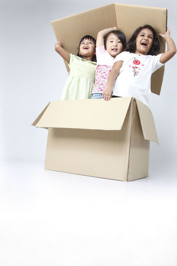 malaysia girl in a box like a house Cardboard Box Fun House Shape Indian Innocence Studio Box - Container Child Childhood Chinese Cover Elementary Age Emotion Front View Full Length Happiness Joy Leisure Activity Malay Malaysia Playful Portrait Shelter Smiling White Background