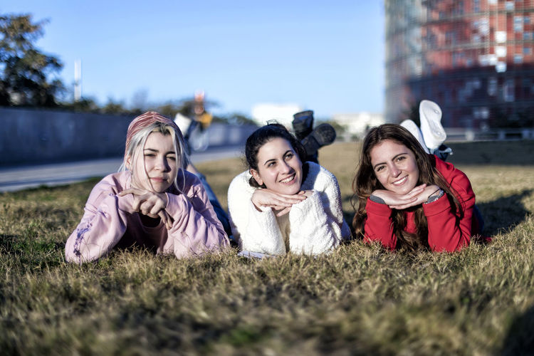 Portrait of three girlfriends lying on the grass in a park in autumn Smiling Group Of People Child Portrait Happiness Women Girls Togetherness Friendship Lying Down Childhood Females Adult Leisure Activity Boys Emotion Looking At Camera Grass Teenager Outdoors Happy Looking At Camera Bestfriend Stundent Females Casual Clothing Young Women Students Denim Stylish City Street Daylight Bright Lifestyle