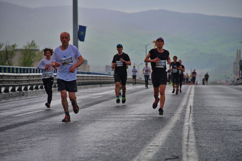 Group of people running on road