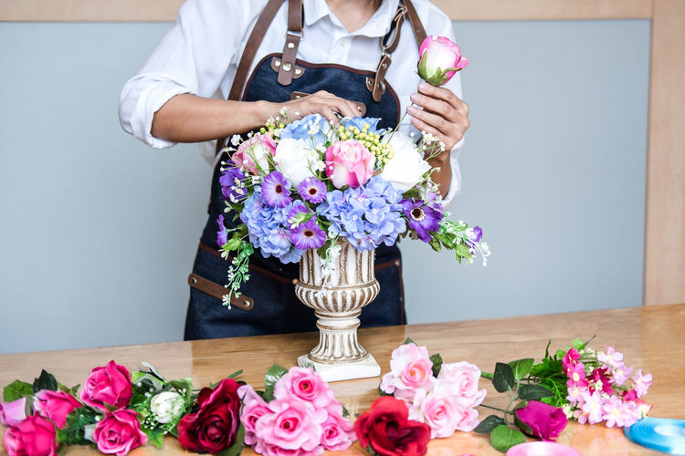 Midsection Of Florist Arranging Flowers In Urn