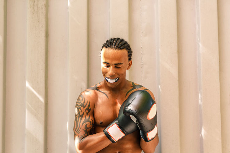 Shirtless man wearing boxing glove while standing against wall