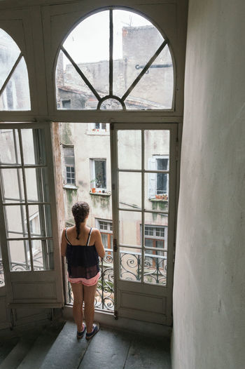Beautiful girl looking out the window Alone Architecture Carcassonne Door Friends Girl Glass Glass - Material Home Interior House Indoors  Leisure Activity Looking Out Millennials Open Pastel Pastel Power Relaxing SA Transparent Wall Window Woman