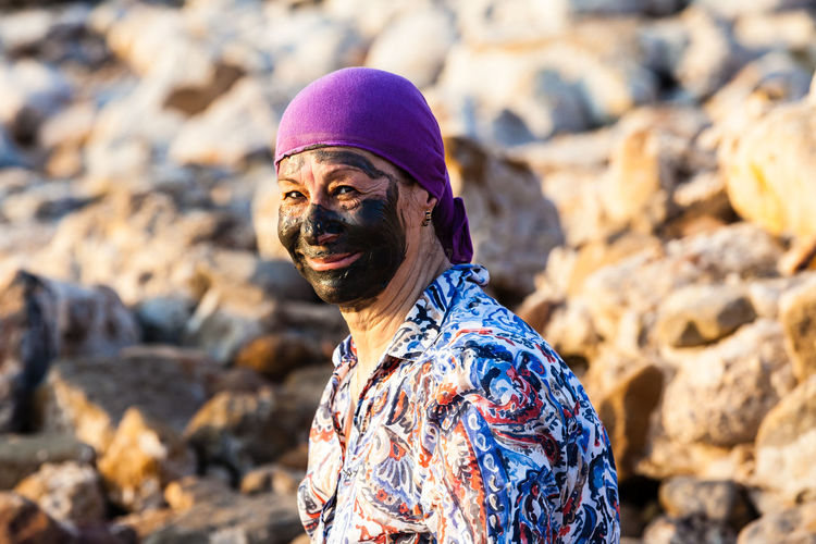 Portrait of senior woman with mud facial mask at rocky shore
