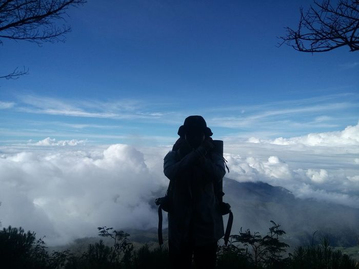 Rear view of silhouette man standing against cloudy sky
