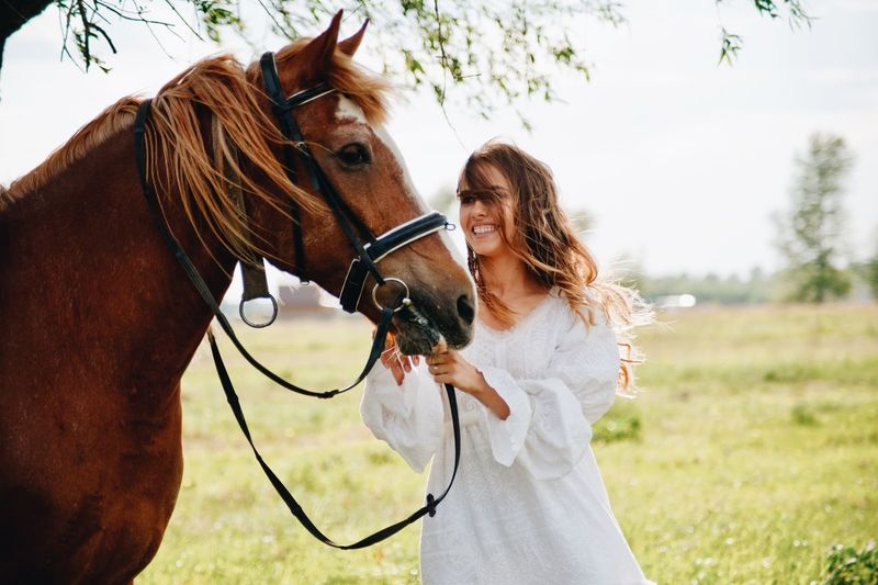 Smiling Woman With Horse Standing On Field