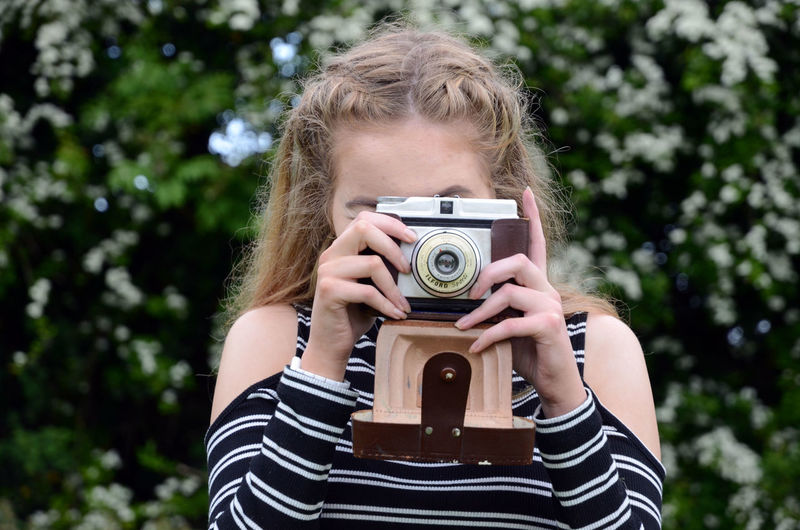 Close-up of woman photographing with vintage camera against trees