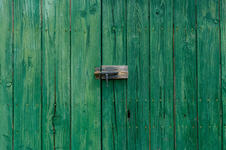 Old wooden door with aged metal door handle. architectural textured background