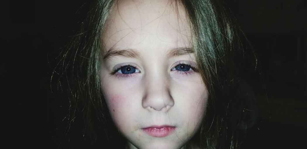 Close-up portrait of girl over black background