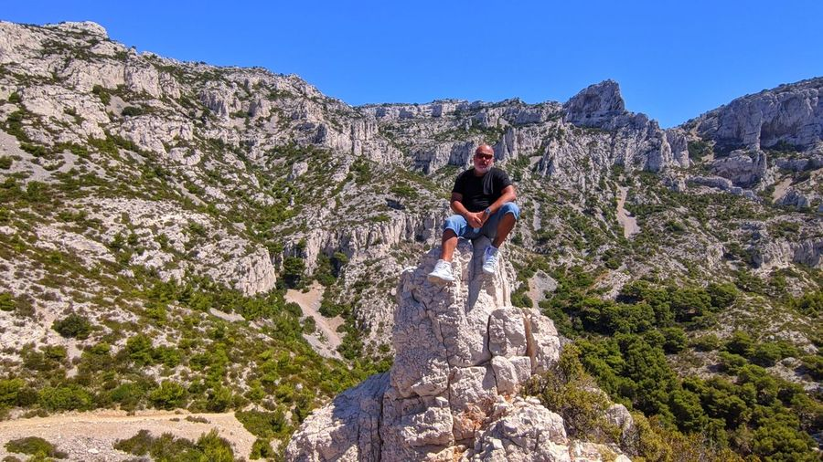 Full length of man on rock in mountains against sky