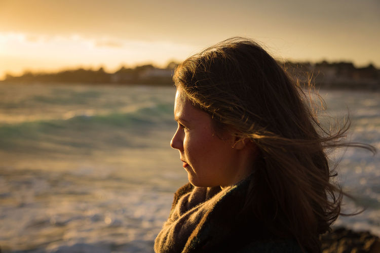 Close-up of young woman looking at sunset