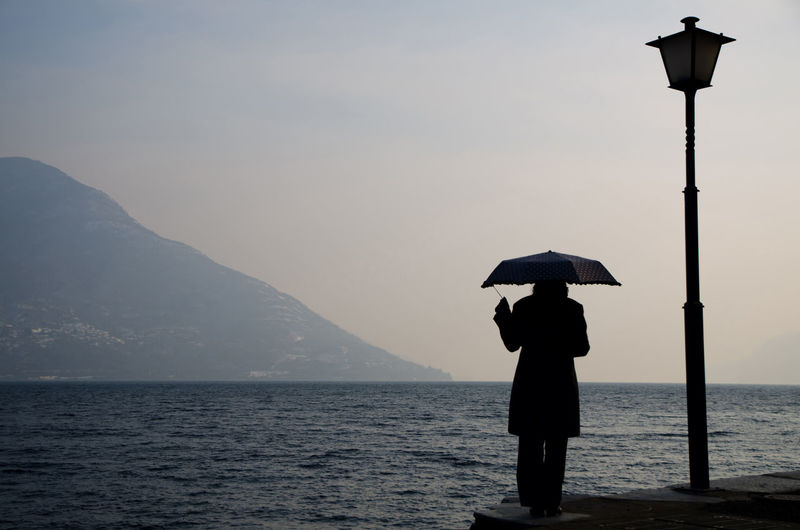Silhouette Woman With Umbrella By Alpine Lake Against Clear Sky At Dusk