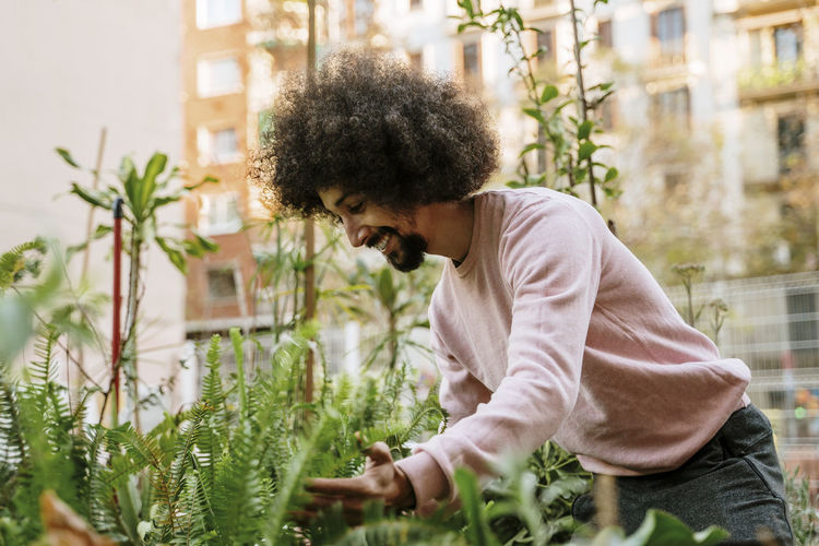 Side view of young man looking at plants