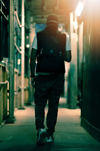 Rear view of man walking on illuminated footpath in city