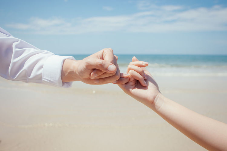 Midsection of couple hands on beach against sky
