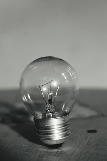 Close-up of light bulb on wooden table against wall