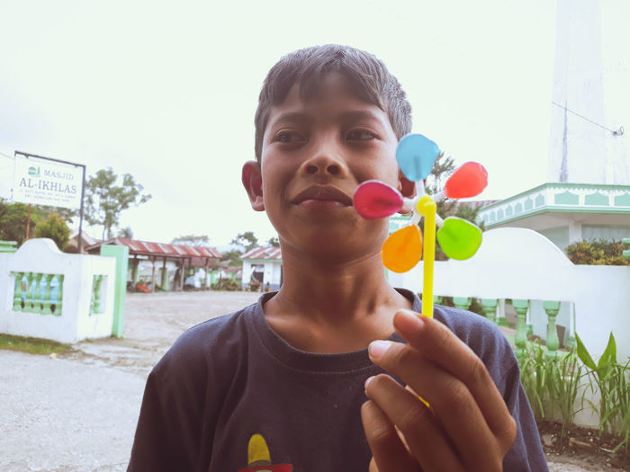 Portrait of boy holding camera against sky