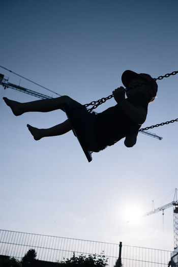Low angle view of silhouette boy enjoying swing against clear blue sky