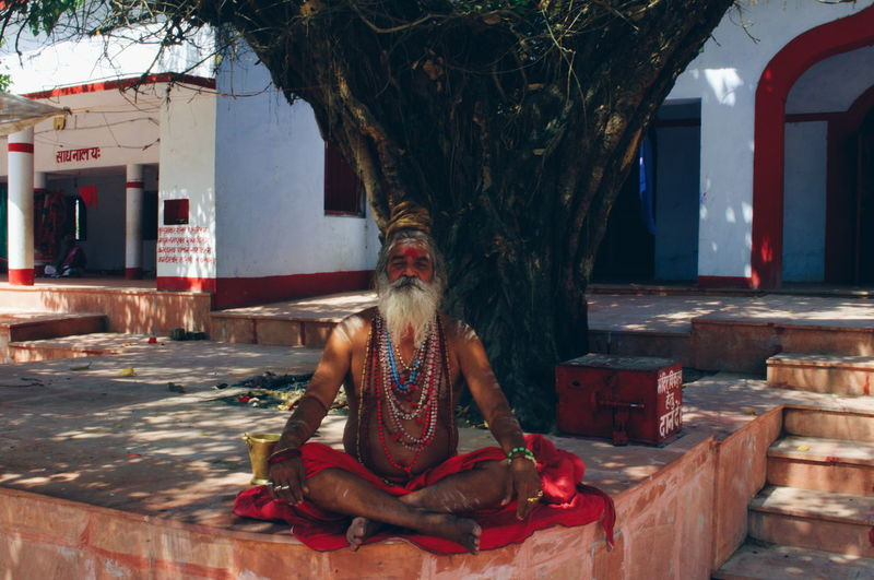 Full length of man sitting in temple against sky