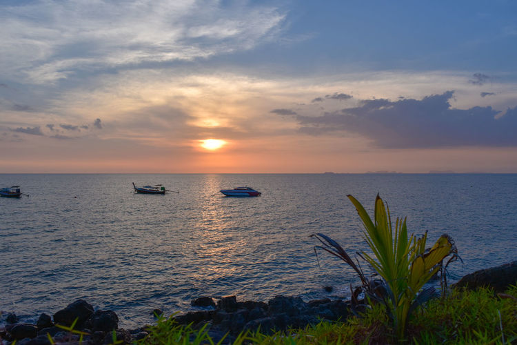 Boats floating in a sunset scenery - tranquility Plant Sunset_collection Beach Beauty In Nature Boat Cloud - Sky Horizon Land Nature No People Scenics - Nature Sea Shore Sky Sun Sunset Sunset #sun #clouds #skylovers #sky #nature #beautifulinnature #naturalbeauty #photography #landscape Water