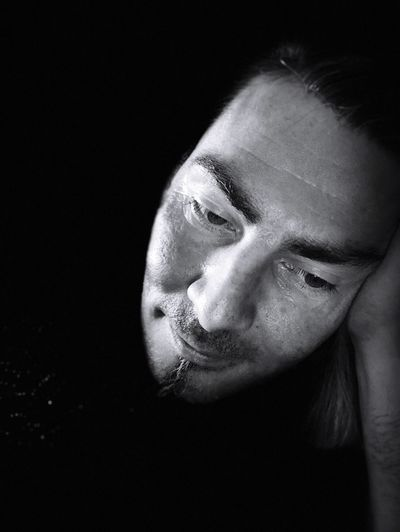 Close-up of man looking down against black background