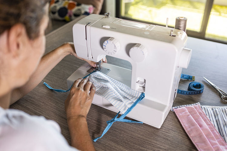 Woman making face masks with a sewing machine at home