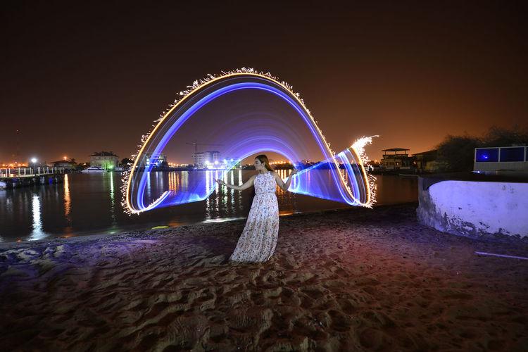 Illuminated ferris wheel in water at night