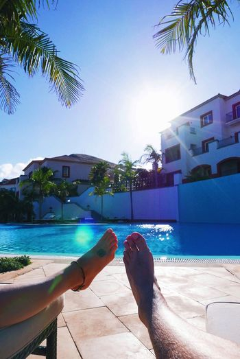 Low Section Of Couple Lying On Lounge Chairs At Poolside