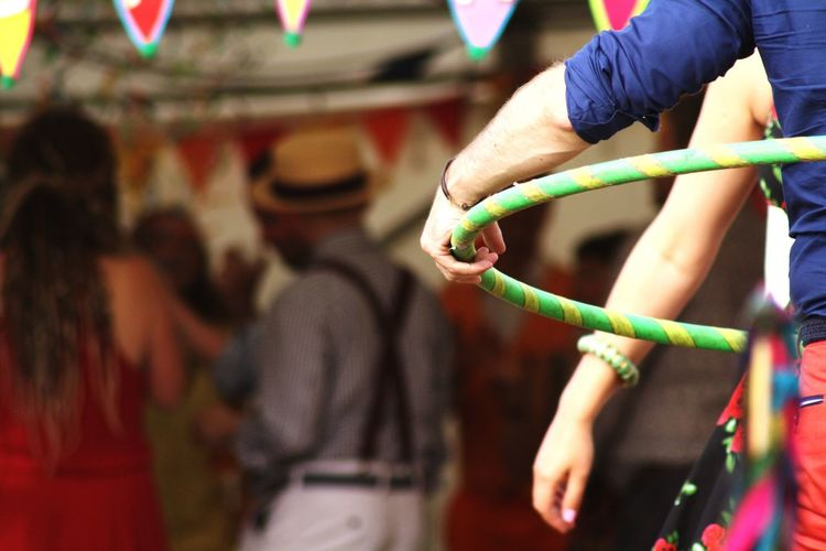 Man Holding Hula Hoop With People In Background At Event