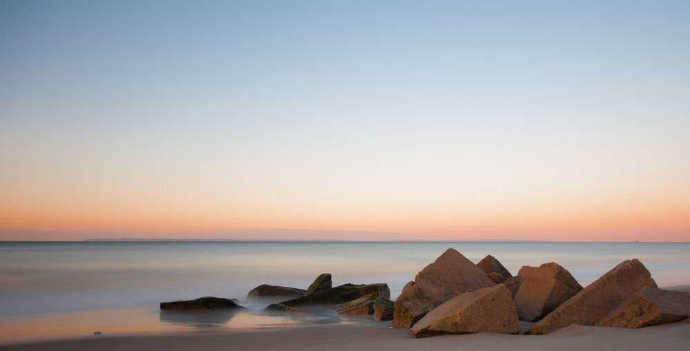 Rocks At Beach Against Clear Sky During Sunset
