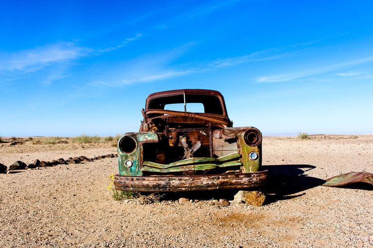 Abandoned vintage car on field against sky