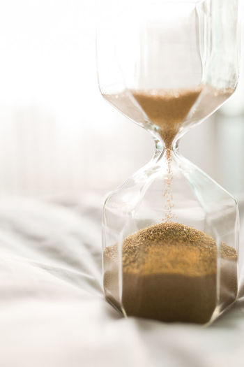 Close-up of hourglass on bed at home