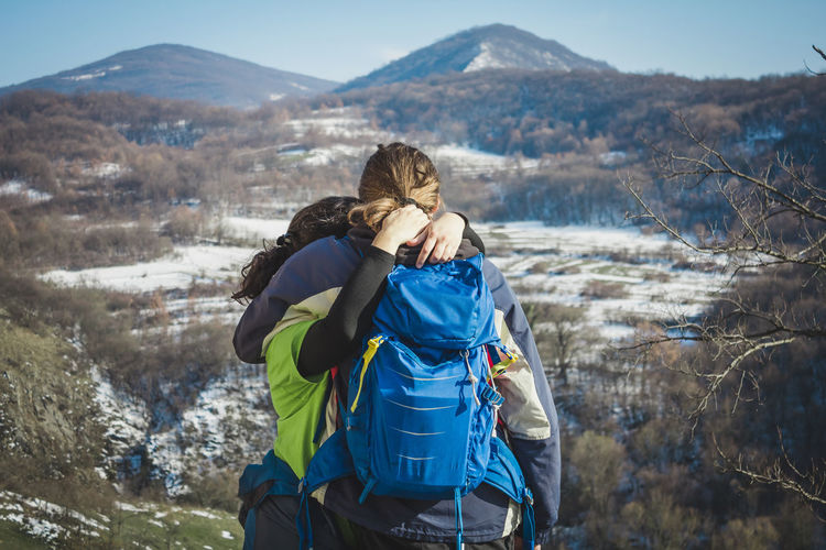 Couple embracing while standing on mountains against sky