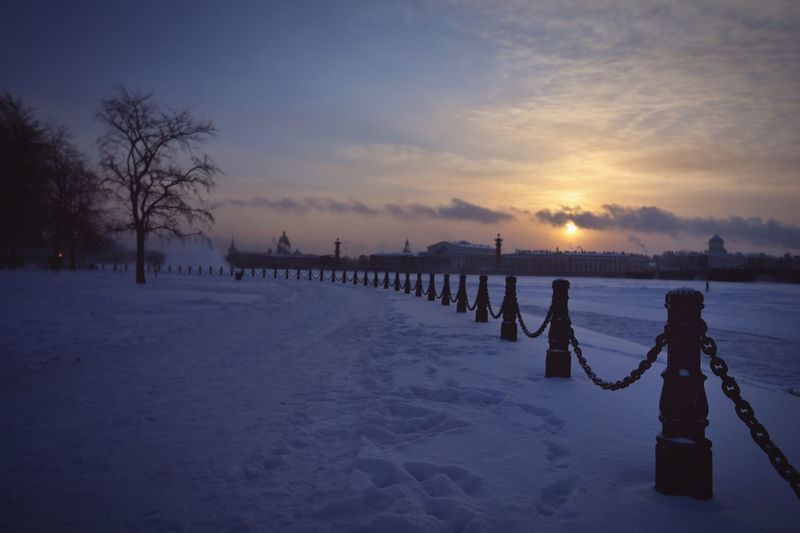 Railing On Snow Covered Field Against Sky During Sunset