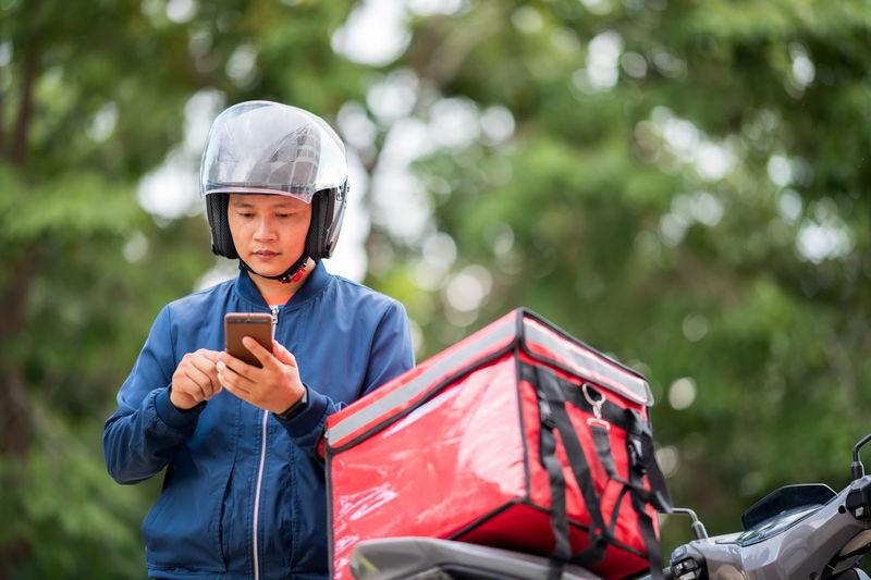 Full length of boy holding mobile phone