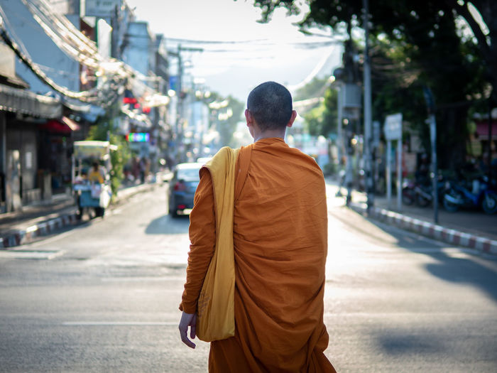 Rear view of monk standing on street