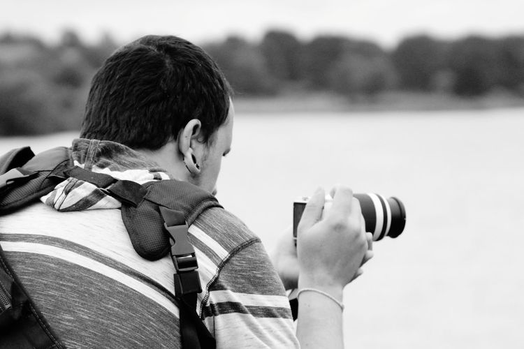 Rear view of man photographing with camera