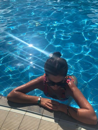 High angle view of young woman wearing sunglasses swimming in pool during sunny day