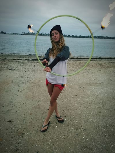 Portrait Of Young Woman With Fire Hula Hoop At Beach Against Sky