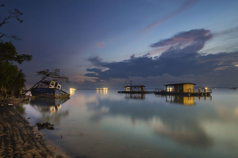 Shipwreck And Stilt House On Lake Against Cloudy Sky At Dusk
