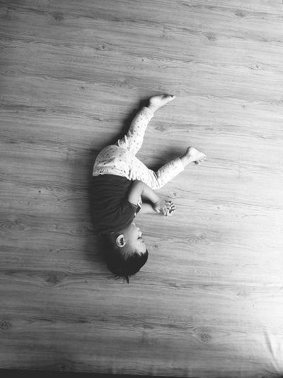 High angle view of boy sleeping on hardwood floor at home