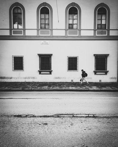 Man walking on road against building