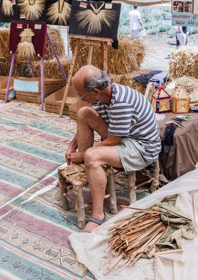 Kibutz Alonim, Israel, June 12, 2016: Elderly man weaves chair at the fair in Kibutz Alonim, Israel Adult Art Artisan Basketry Cane Craft Craftsman Craftsmanship  Day Design Experience Expert Hand Handmade Making Man People Person Product Skill  Tradition Weave Wicker Woman Work