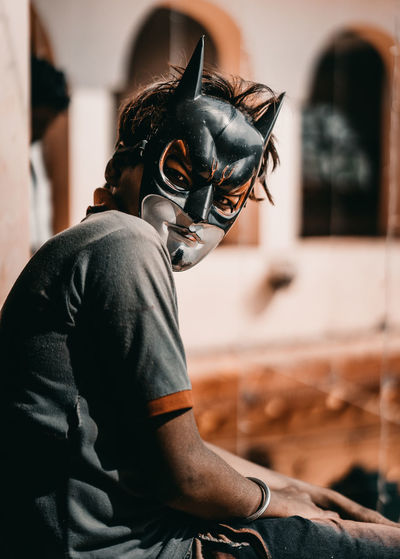 Portrait of man wearing mask at home